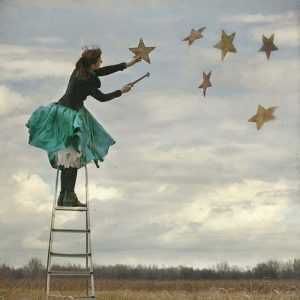 woman wearing fairy outfit and crown releasing stars into the sky to answer what is coaching