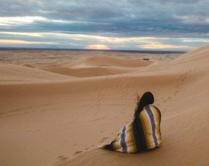 woman wearing mexican blanket sitting in meditation on sand dune to answer what is meditation