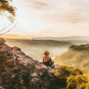 woman sitting on mountainside overlooking lush valley asking question what is a retreat