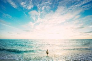 woman standing in turquoise ocean gazing a bright sunrise in deep blue sky pondering Life Coach for Personal Development