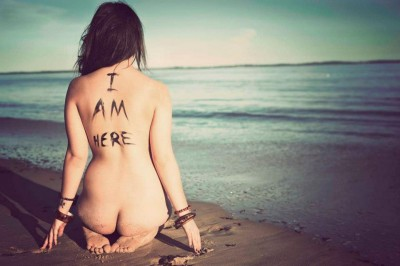 A naked woman sitting on the beach facing away from camera, words I AM Here on her back loving the body as it is and embodying the wild sacred feminine
