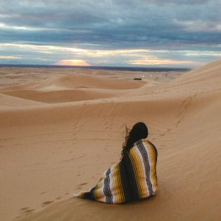 woman in mexican blanket on sands watching sunrise what is meditation