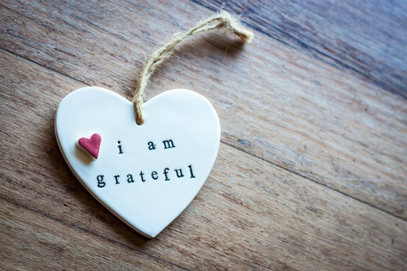 a hanging heart ornament with stamped words I am grateful.