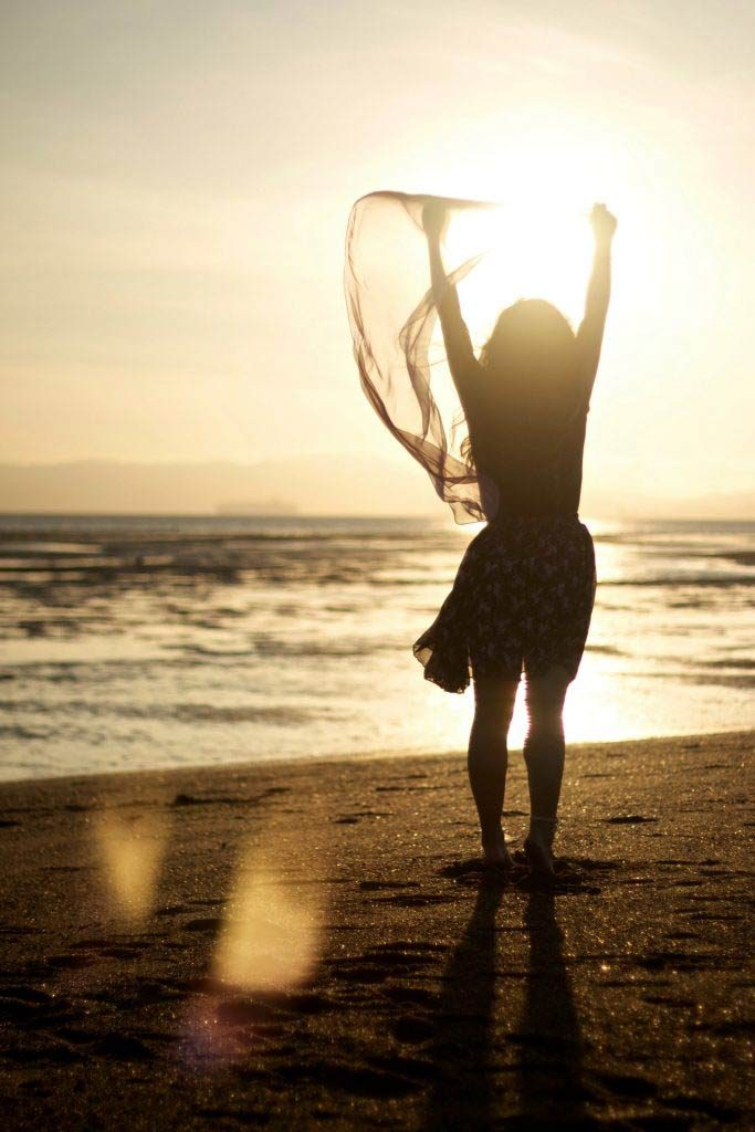 joyful woman on beach facing bright sunrise with her arms raised benefit of life coach for personal development